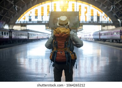 Young traveler walking with backpack on train station and waitin