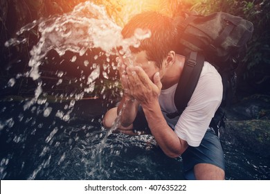 Young traveler washing his face in the wild river (intentional sun glare and motion blur)