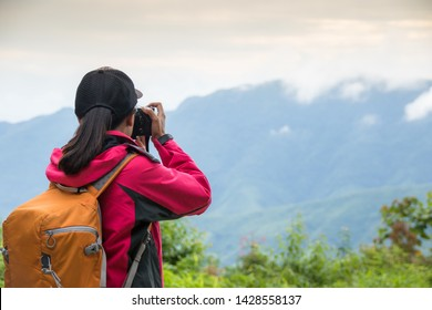 The young traveler wears a pink shirt. She is taking pictures of national scenes in the morning of the rainy season with a mist on the mountain.
