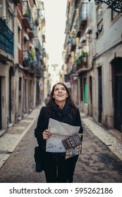 Young traveler woman admiring beautiful sunny narrow streets in Lisbon, Portugal.Sunny day in Lisbon,traveling in Europe.Backpacker photographer reading map for navigation and moving around city
