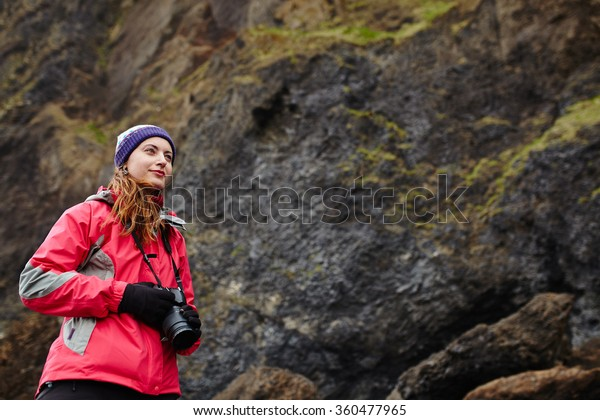 Young traveler woman holding camera in Iceland. Beautiful caucasian woman photographer wearing winter clothes on rock background.