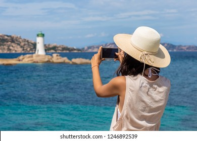 Young traveler woman making photo with mobile phone camera of lighthouse in Italy. Travel concept
