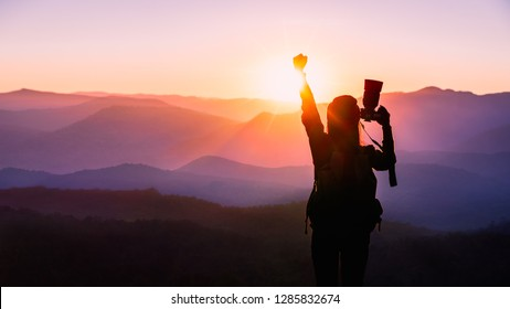 Young traveler woman raise hands up for her success with sunset on mountain natural background.