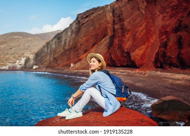 Young traveler woman relaxing sitting on Red beach rock on Santorini island Greece admiring seaside view, mountain landscape. Tourist enjoys summer vacation - Shutterstock ID 1919135228