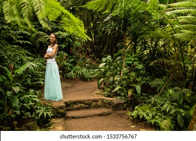 Young traveler woman walking in tropical forest. Travel lifestyle. Caucasian woman wearing long light blue skirt and white top. Green jungle trekking. Luxury vacation. Trip to Ubud, Bali, Indonesia.