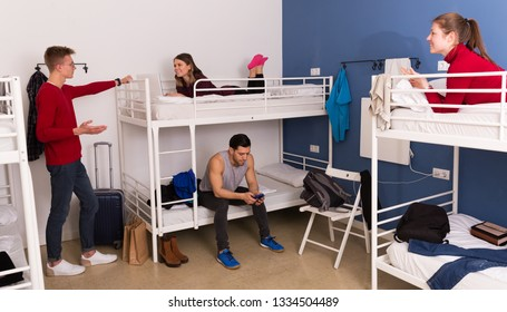 Young travelers communicating while resting in hostel bedroom
