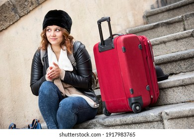 young traveling girl is sitting on a stairway wearing winter clothes and a red trolley trying to warm up to shelter from the cold