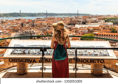 Young traveling woman walking on the streets of Lisbon city and looking at beautiful view