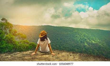 Young traveling woman wearing hat and sitting on the top of the mountain cliff with relaxing mood and watching beautiful view of woods and blue sky and clouds on vacation. Asian woman travel alone.