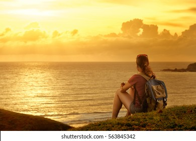 Young traveller with backpack enjoying sunset listening to music on peak of mountain.