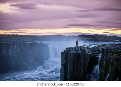 Young traveller female on top of cliff near Hafragilsfoss Waterfall in Iceland
