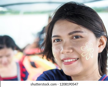 Young traveller girl selfie on the boat with Tanaka on her smile face is happiness. Tanaka is a yellowish-white cosmetic paste made from ground bark.