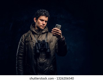 Young traveller in hiking gear with binoculars uses GPS navigation on his smartphone in the studio against a dark wall