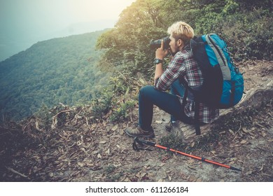 Young traveller hiking love adventure sitting on the top of mountain after hiking. Safety trip with travel insurance. traveller concept.