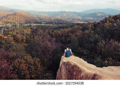 Young traveller sitting on the edge of mountain hill over sunset view.