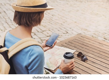 Young traveller woman sitting in a cafe terrace and planning trip with map and smartphone. Travel and active lifestyle concept
