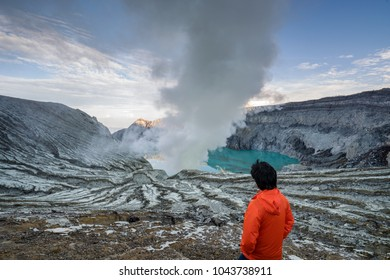 Young travler looking at Sulfur burned by blue flame in the crater blue lake at Kawah Ijen, Indonesia