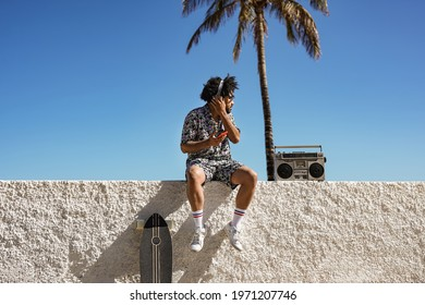Young trendy african man enjoy music playlist in summer vaction in the city - Skater boy with retro boombox outdoor