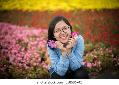 Young trendy asian bespectacled teenager with palms around face and holding flowers petals smiles broadly. Photo with vignetting and meadow as background.