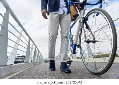 young trendy black african hipster man with bicycle walking in urban city on way commute to work