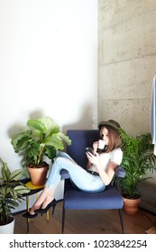 Young trendy brunette in hat and heels sitting in armchair drinking coffee and browsing phone.