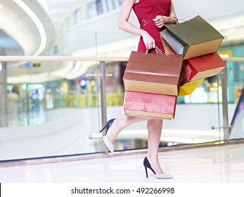 young trendy and fashionable woman female shopper carrying colorful paper bags walking in modern shopping mall