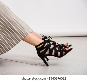 Young and trendy female legs with black high heeled shoes with heels on the ground. Studio abstract shot, body parts.