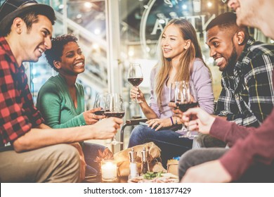 Young trendy friends drinking red wine inside fashion winery bar - Happy people haing fun and laughing together in pub restaurant - Youth and nighlife concept - Soft focus on blond girl glass