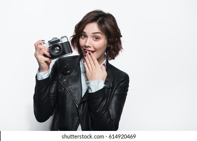 Young trendy girl in black leather coat holding retro photo camera and looking at camera on white.