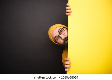 Young trendy hipster in hat and eyeglasses standing behind yellow paper screen looking excited.