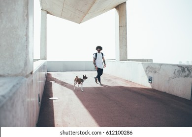 Young trendy hipster with tattoos crazy curly hair walks in a very urban city environment with his best friend, a little brown dog