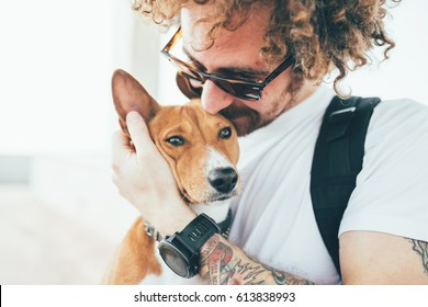Young trendy hipster with tattoos crazy curly hair with his best friend a cute small basenji puppy gives him a tender kiss on ears while hugs him with his arms