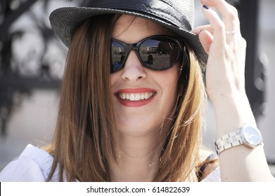 Young and trendy hipster woman wearing a hat and sunglasses. Lifestyle concept.