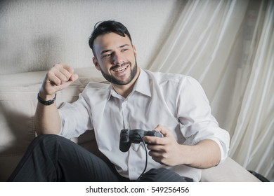 young trendy male gamer playing with a joystick