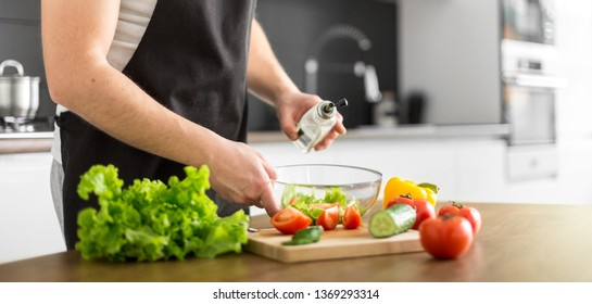 Young trendy man cooking healthy food in the morning