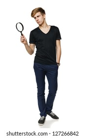 Young trendy man in full length looking trough the magnifying glass, over white background