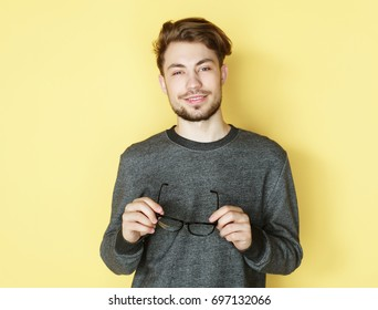Young  trendy man with glasses smiling, studio shot
