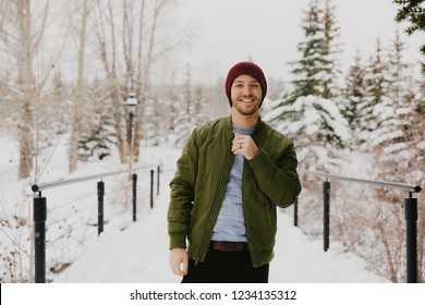 Young Trendy Man in Green Bomber Jacket Enjoying the Winter Snow on a Small Bridge in Colorado