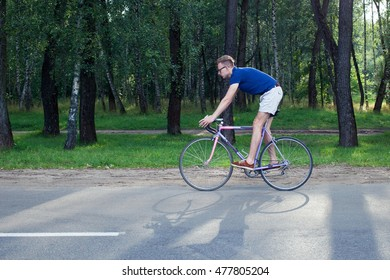 Young trendy man riding a bike in the park