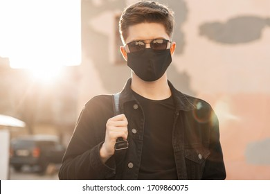 Young trendy man in youth casual clothes in sunglasses in protective black mask walks on city at sunset. Fashionable teenager guy enjoys in bright sunlight. Spring. Modern Fashion 2020.