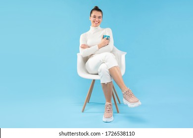 Young trendy positive girl sitting in armchair, holding coffee cup in hands, enjoying her free time from work, isolated on blue background