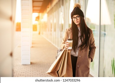 Young trendy woman blogger with shopping bag and smartphone near mall
