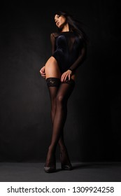 Young trendy woman in lingerie bodysuit and stockings posing on dark background