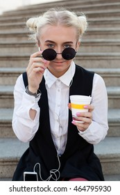 Young trendy woman in sunglasses listening to music and drinking  coffee