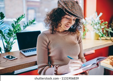 Young trendy woman writing organisation plan in textbook after e learning on netbook spending time at coworking space, positive female journalist creating list of meetings and interviews for next week