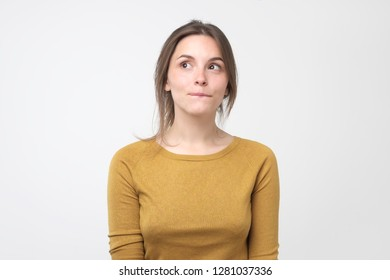 Young tricky woman having something in mind with sly facial expression