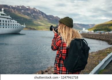Young trndy millennial hipster, blonde woman in red shirt and green beanie makes photos of huge cruise ship entering fjords in iceland or norway. Travel blogger explores world