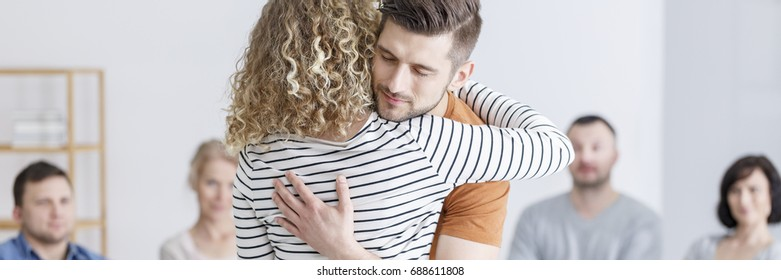 Young troubled couple hugging and making up during therapy
