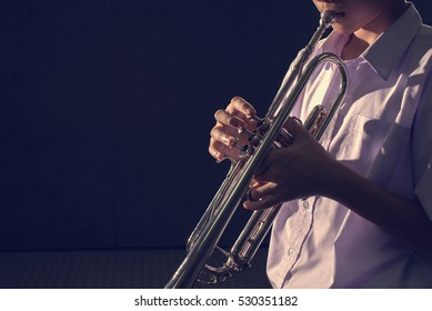 young trumpet player in dark