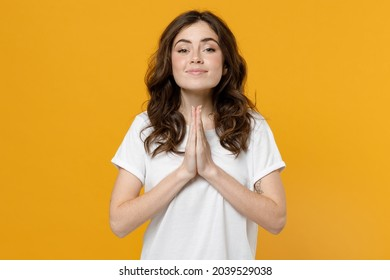Young trustful pleaded caucasian student woman 20s wearing white basic casual t-shirt hands folded in prayer gesture, begging about something isolated on orange yellow color background studio portrait